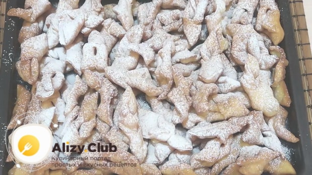 Для приготовления хвороста на сметане по рецепту, посыпьте печенье сахарной пудрой
