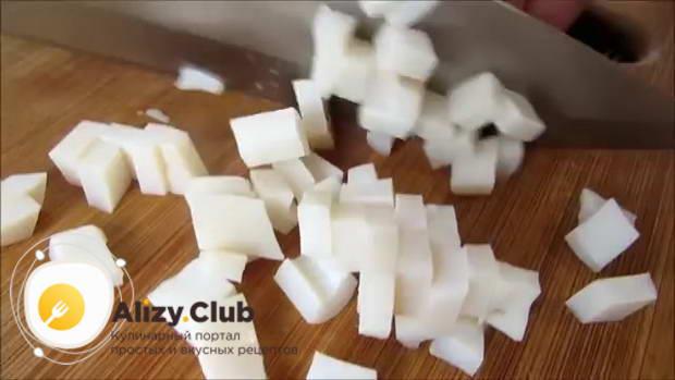 Нарежьте кубиками 2 отваренных и остуженных кальмара