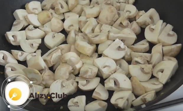 После лука выкладываем на сковороду грибы и обжариваем до готовности.