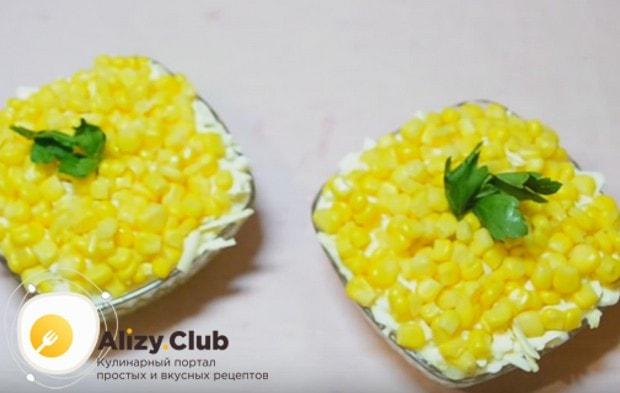 Салат со шпротами и кукурузой можно украсить свежей зеленью.